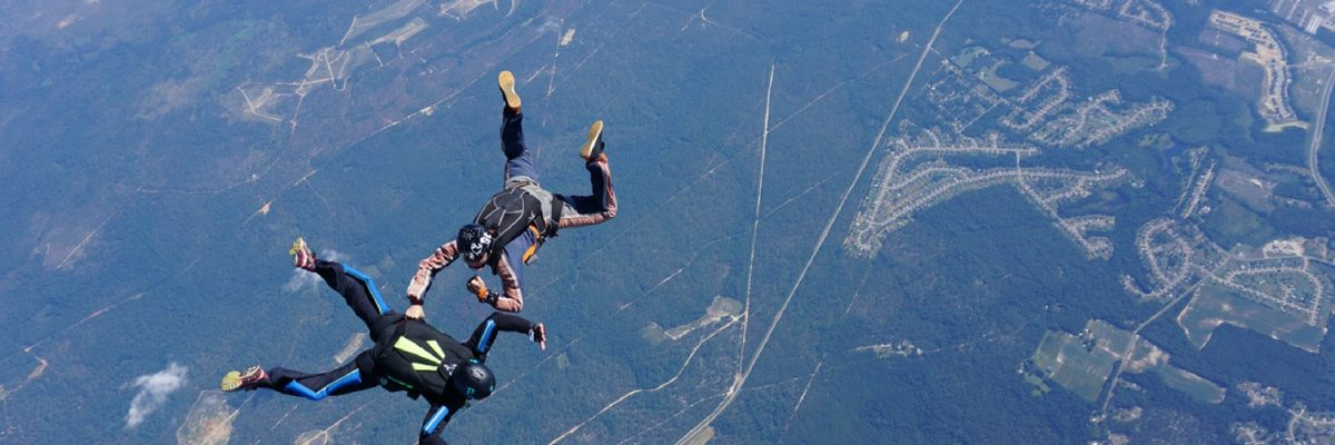 learn to skydive student flies receives hands-on attention from instructor in freefall