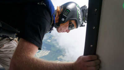 A skydiver exits the aircraft using an audible altimeter.