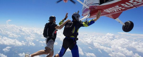 student exits plane alongside skydiving instructor