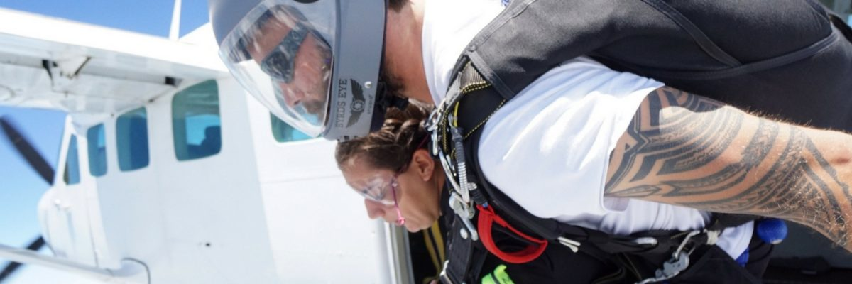 woman faces her fear of skydiving in the door of the airplane