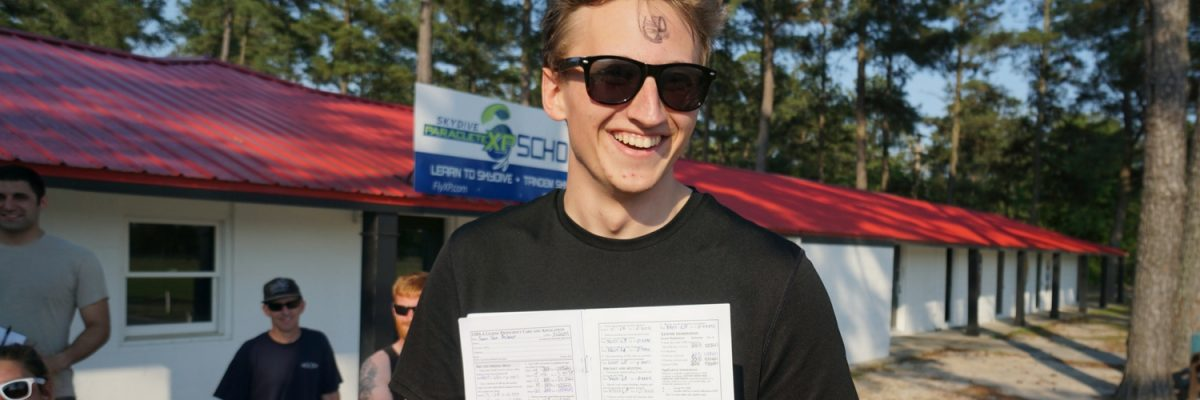 student beams with skydiving license in hand