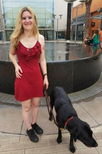 Shawnna in front of fountain with seeing eye dog