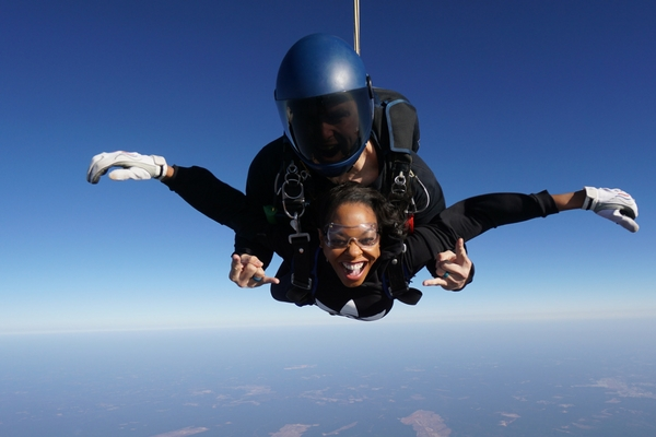 woman smiles ear to ear tandem skydiving first time