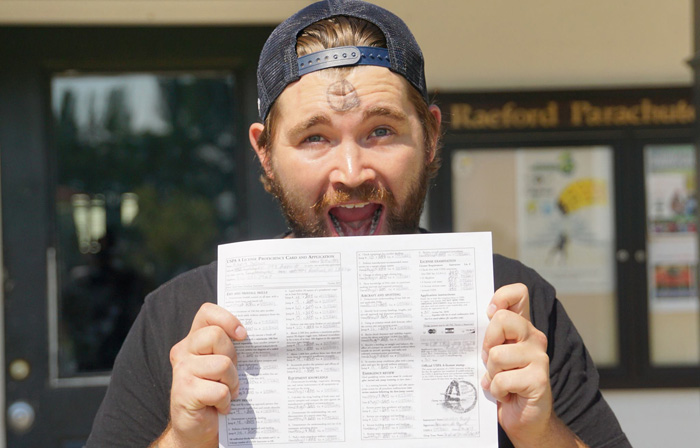 Skydiver holding his A License skydiving certification
