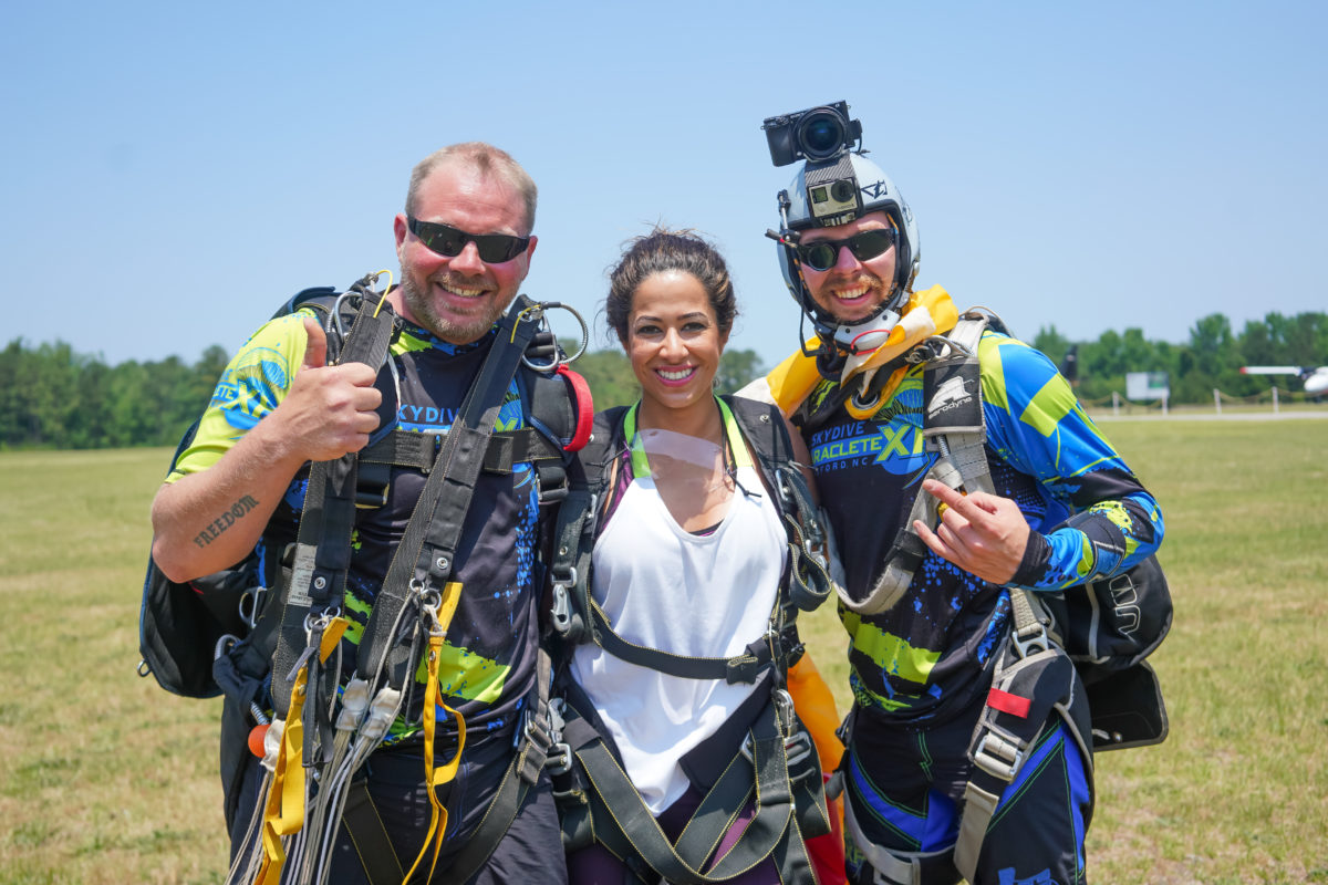 Three skydivers celebrate after a landing.