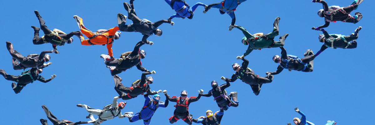 A group of skydivers fly in the air