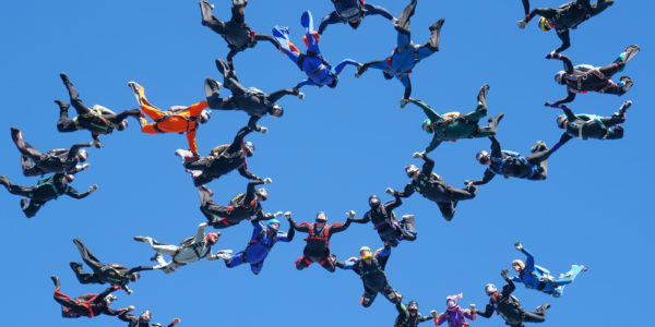 A group of skydivers fly in the air.