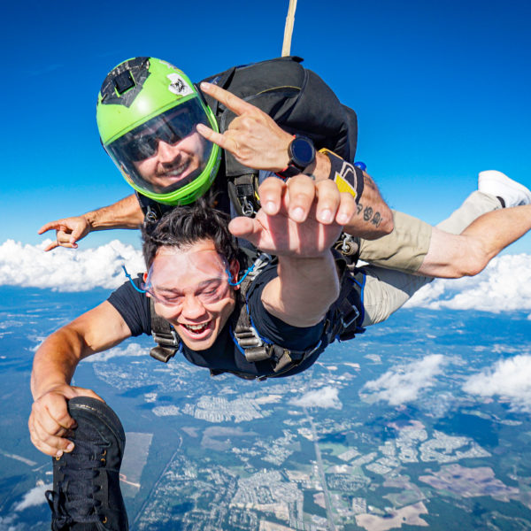 A tandem student smiles from ear to ear during free fall.
